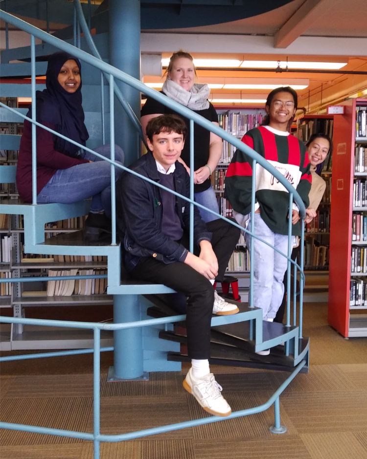 The UWinnipeg Library student assistants sit on a spiral staircase.